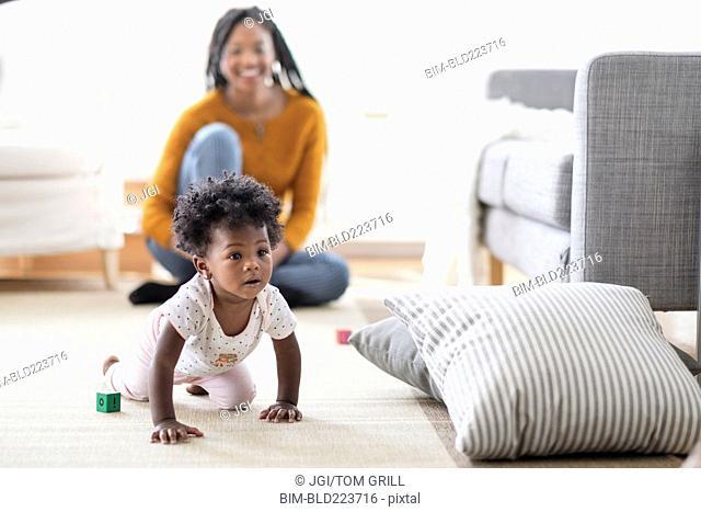 Black woman watching baby daughter crawl toward pillow