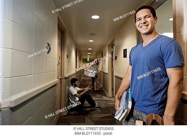 Caucasian student smiling in dorm hallway