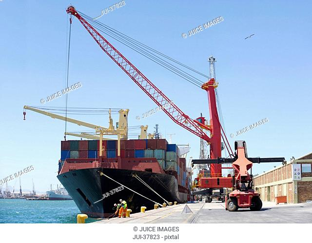 Cranes unloading container ship at commercial dock