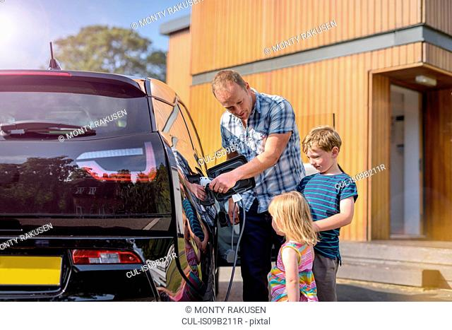 Father with children, charging electric car