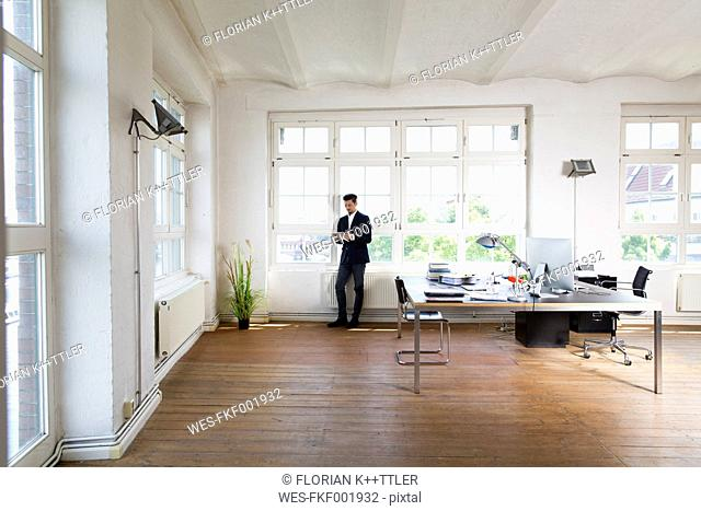 Businessman standing at window reading messages