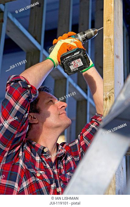 Electrician drilling wooden frame on building construction site interior