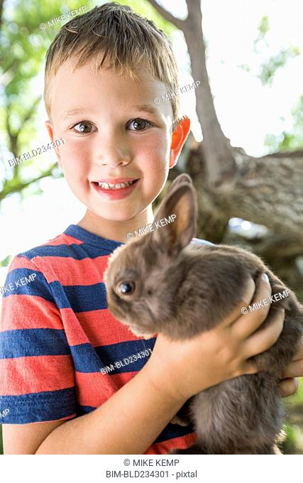 Caucasian boy holding rabbit