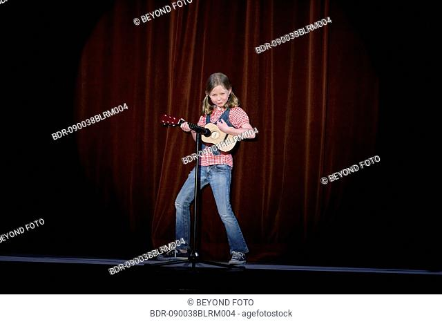 young girl playing guitar on stage