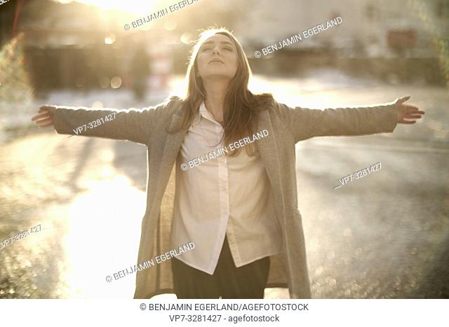 young woman outdoors in sunlight at street in city, in Cottbus, Brandenburg, Germany