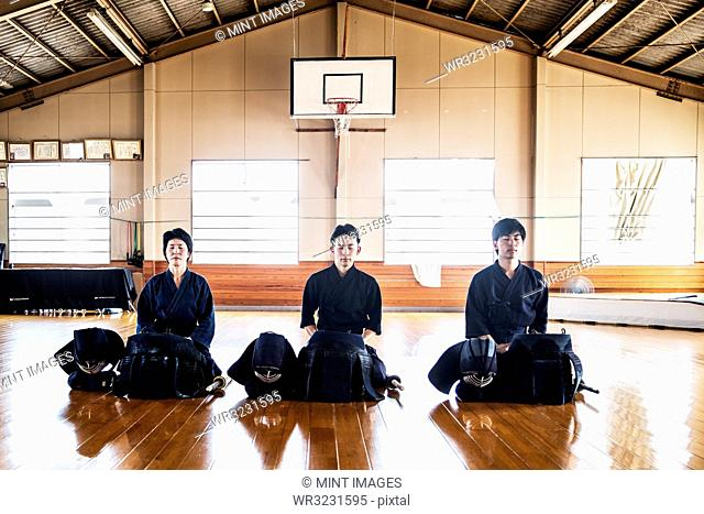 Female and two male Japanese Kendo fighters kneeling on wooden floor, meditating