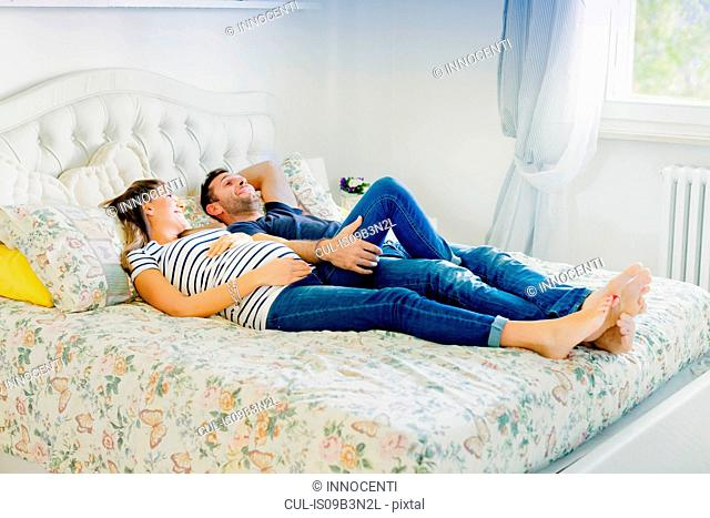 Pregnant couple lying on bed smiling