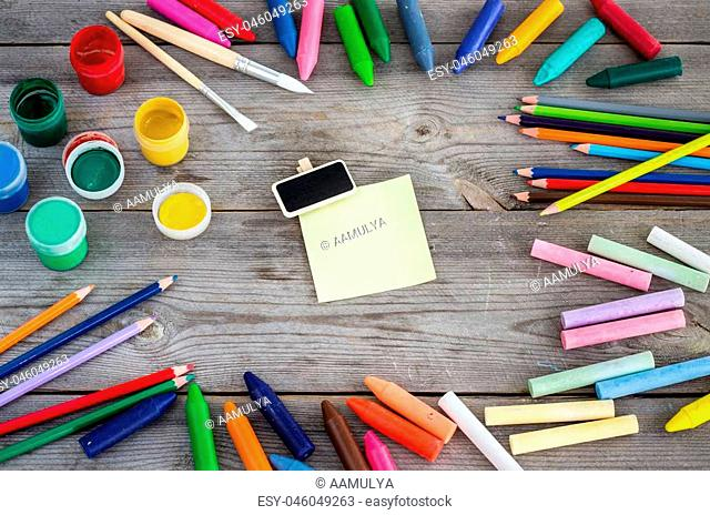 Education and business concept. School supplies with crayons, paint, chalk on a copy space wooden background. Selective focus
