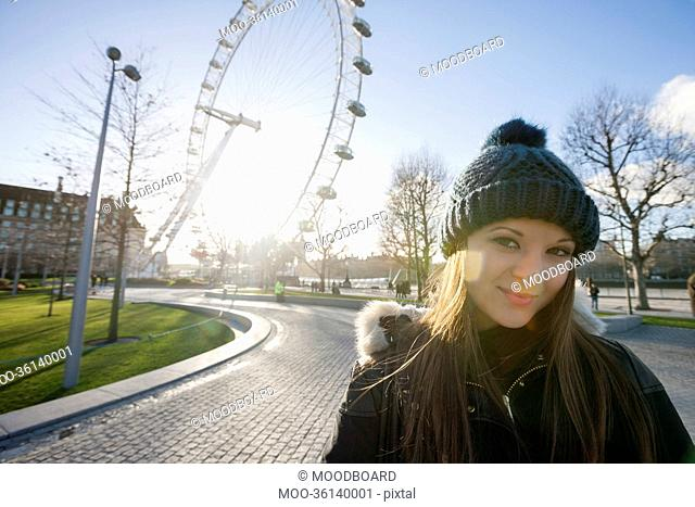 Portrait of beautiful young woman in front of London Eye, London, UK