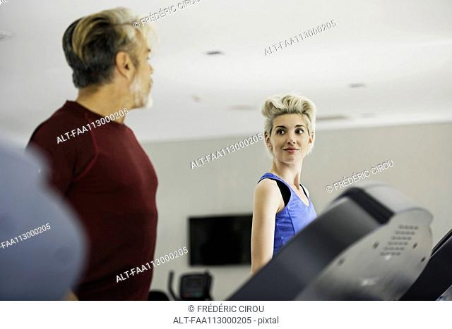 Man and woman exercising on treadmills