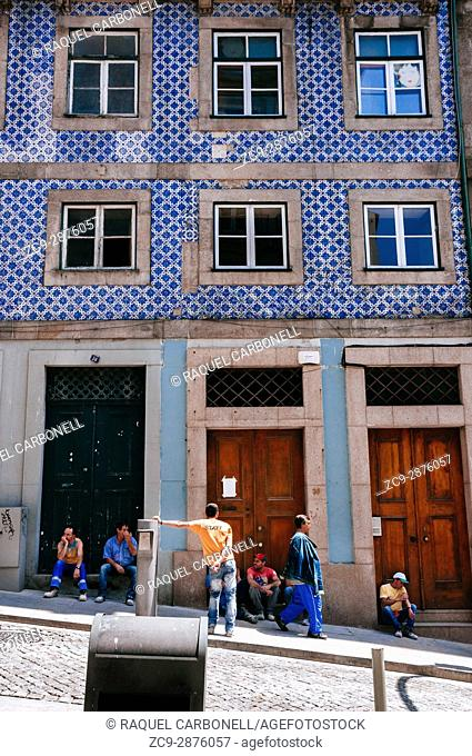 Workers sitting and talking at house doorway, Porto, Portugal
