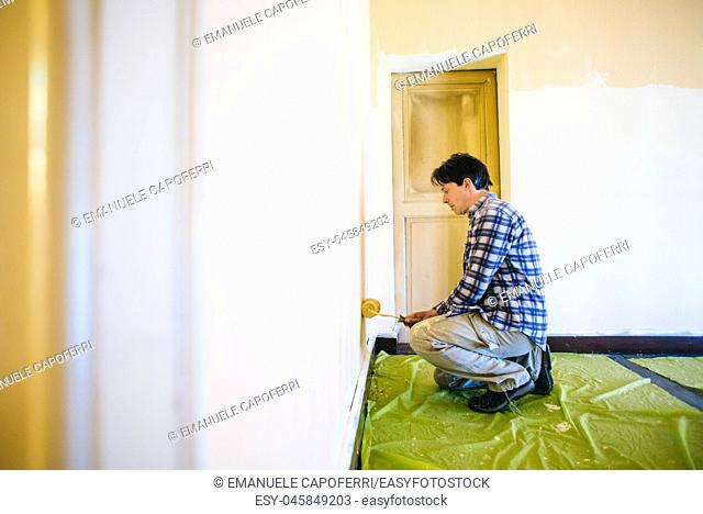 husband father of forty years, paints house wall - man painting wall of a room-man performs DIY painting at home
