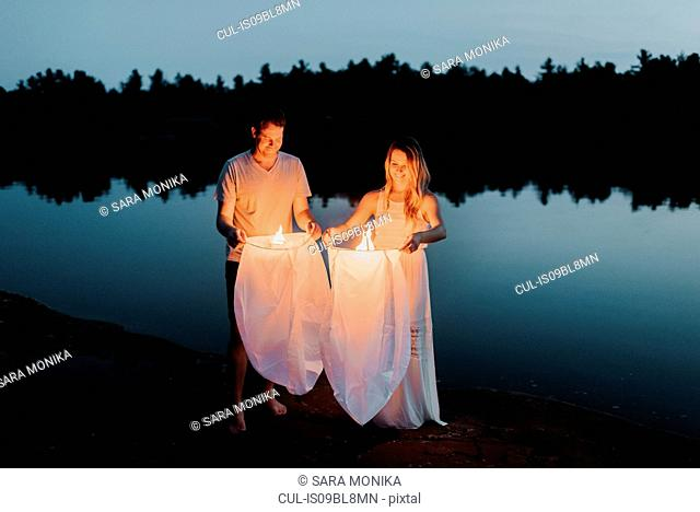 Couple releasing sky lanterns by lake, Algonquin Park, Canada