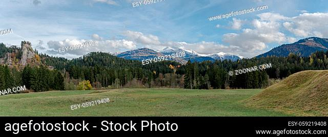 panorama landscape view of green pastures and forest in fall colors with snow-capped mountains behind in the Alps of Switzerland in the Surselva near Flims