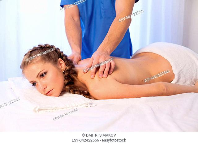 beautiful girl massage therapist makes a back massage in the spa health 1