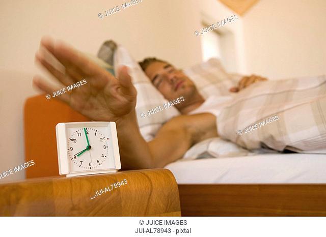 Man hitting snooze on his alarm