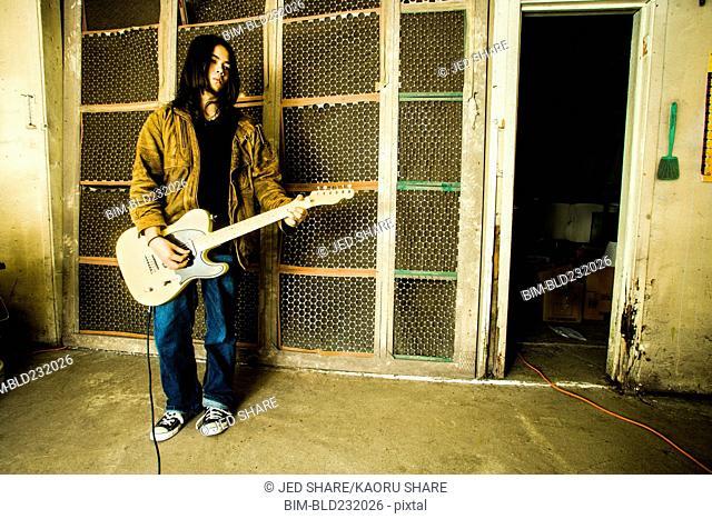 Mixed Race man playing electric guitar outdoors