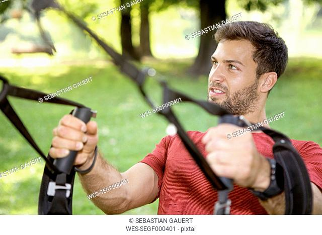 Portrait of sportive man doing TRX training in a park