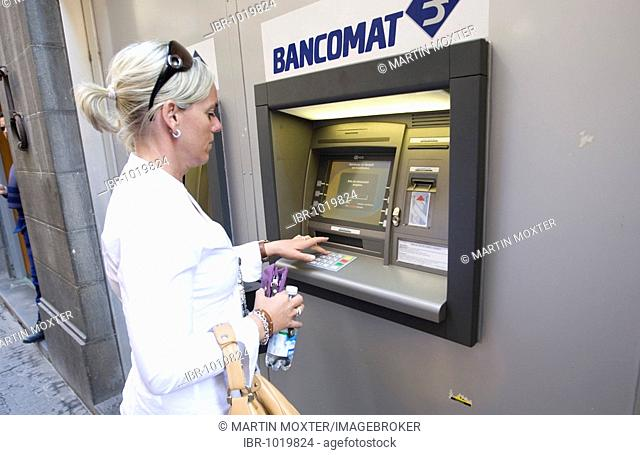 Woman getting money from a cash machine in Siena, Tuscany, Italy, Europe
