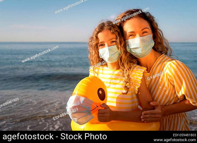 Happy mother and daughter wearing medical mask outdoor against blue sky background. Woman and child enjoying by sea at summer
