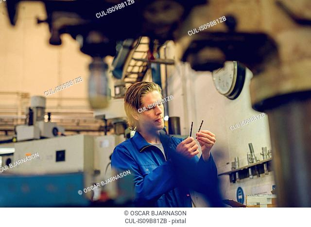 Factory worker wearing protective clothing, inspecting manufacturing machine part