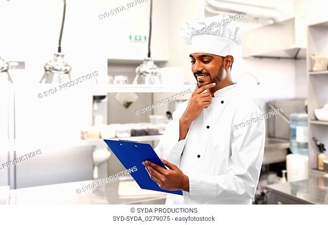 indian chef with clipboard at restaurant kitchen