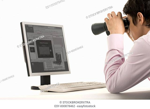 Photo of white collar worker with binoculars looking at monitor of computer