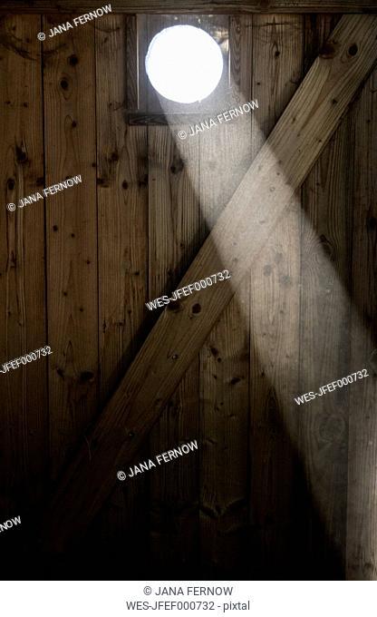 Ray falling through oculus of wooden door