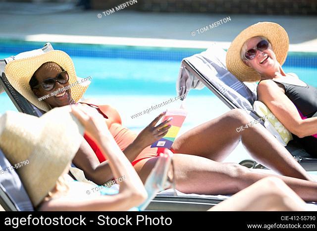 Happy senior women friends sunbathing at sunny summer poolside
