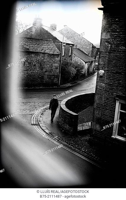 View through a window of a street with a man walking in Grassington, Yorkshire Dales, England, UK, Europe