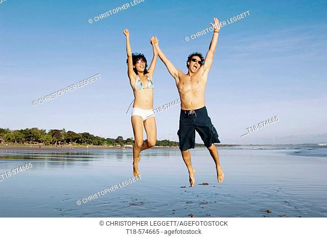 couple playing and jumping on beach
