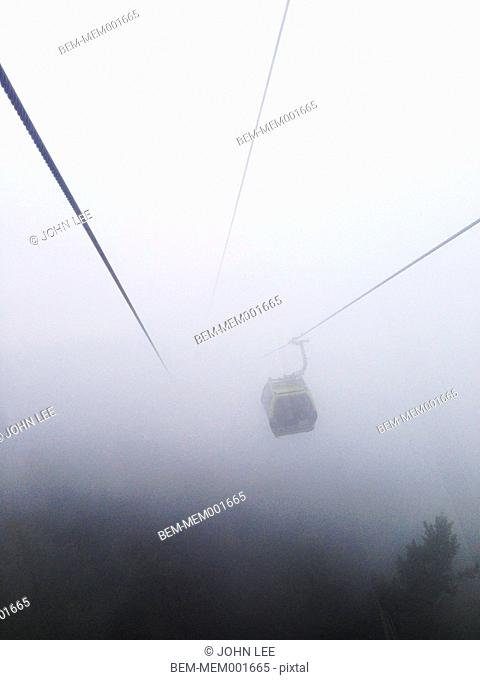 Gondola hanging from suspension cables in fog