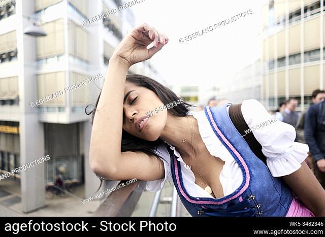 Brazilian woman wearing Dirndl, leaning on railing, exhausted. Munich, Germany