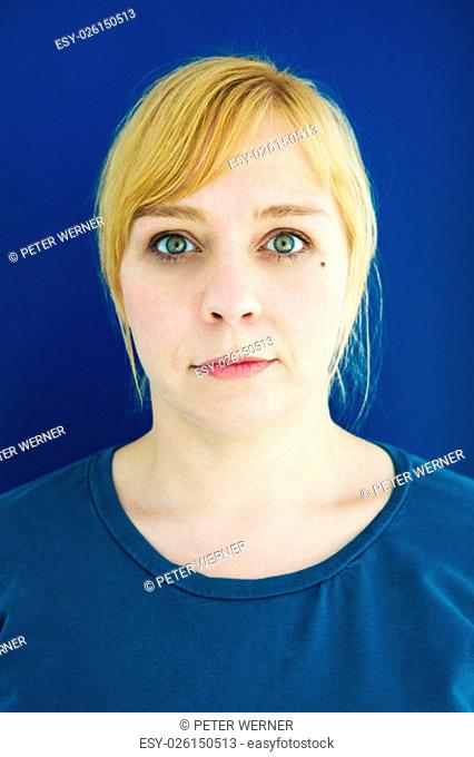 portrait of young blond woman with blue background