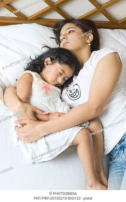 Woman resting on the bed with her daughter