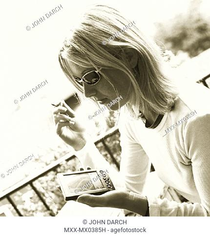 Blonde woman with palm pilot at cafe in Italy