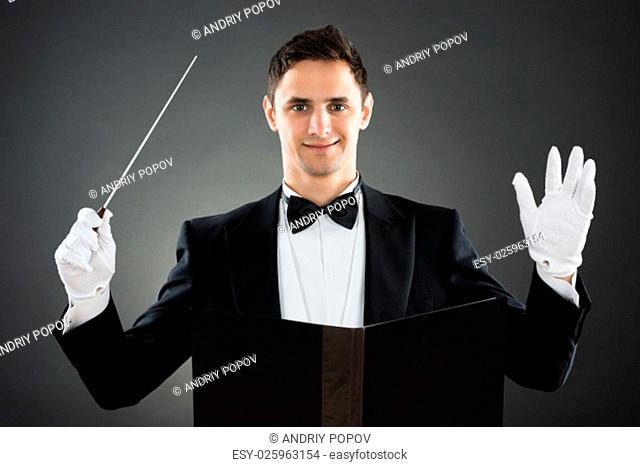 Portrait of smiling music conductor holding baton against gray background
