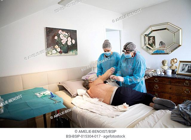 Reportage on a home health care service in Savoie, France. A nurse and auxiliary nurse place a VAC therapy dressing on a pulmonectomy