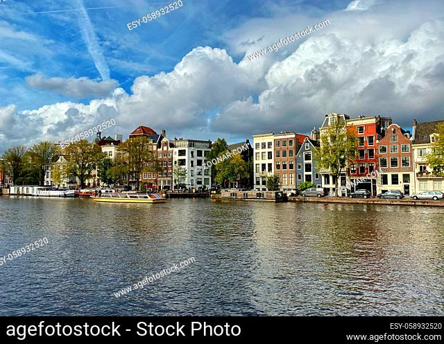 Amsterdam, Netherlands - October 2, 2019: Amsterdam canal with typical dutch houses and houseboats, boats in the evening with beautiful water reflections