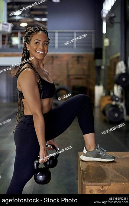 Smiling female athlete lifting kettlebells while standing in gym