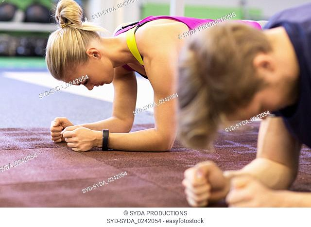 woman and man doing plank exercise in gym