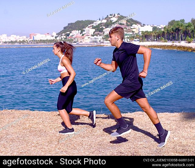 Athletes boy and girl practicing running on the seashore in thei