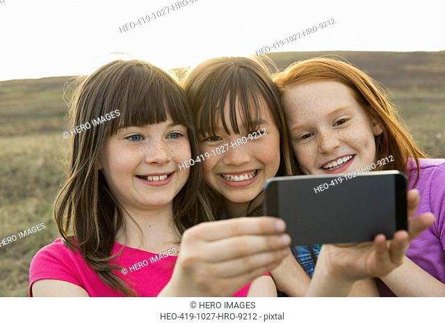 Schoolgirls photographing through smart phone during field trip