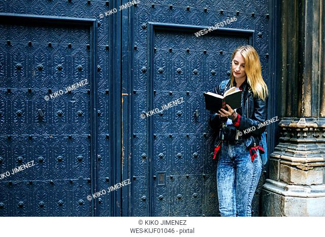 Spain, Barcelona, young woman standing in front of blue entrance gate reading a book
