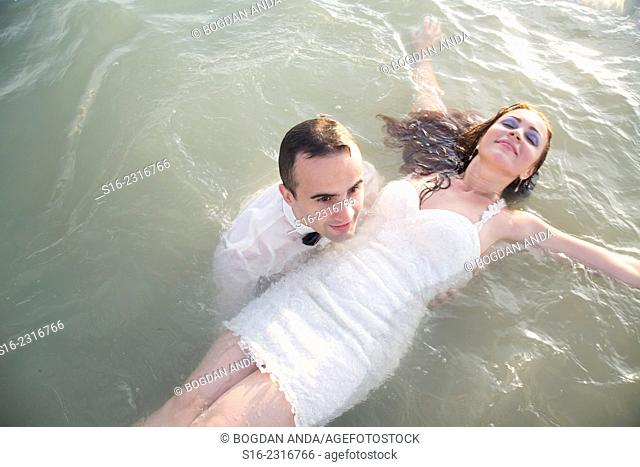 Young man dressed up in a party suit, holding afloat in shalow sea a young woman in a white party dress