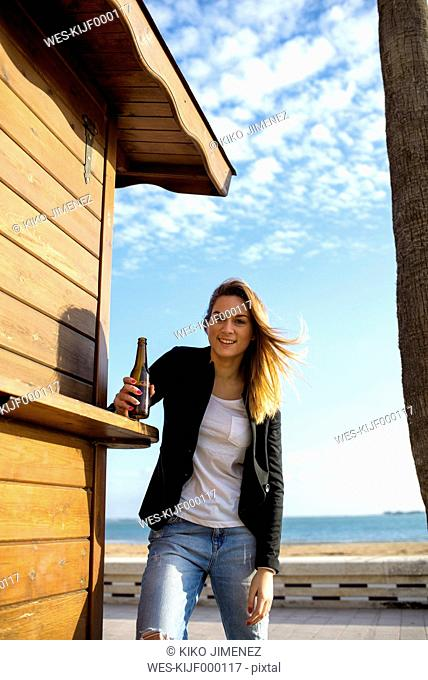 Spain, Puerto Real, portrait of relaxed woman with bottle of beer standing besides a beach hut