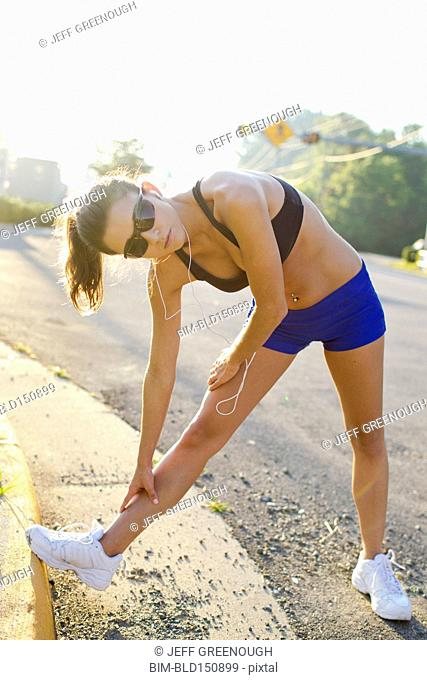 Caucasian runner stretching on curb