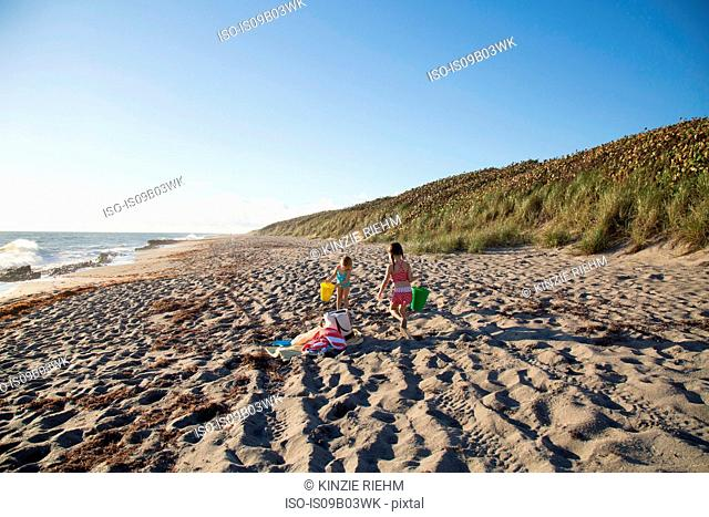 Two sisters playing with toy buckets on beach, Blowing Rocks Preserve, Jupiter Island, Florida, USA