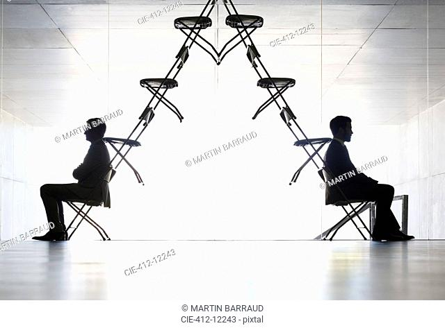 Businessmen sitting at opposite ends of office chair installation art