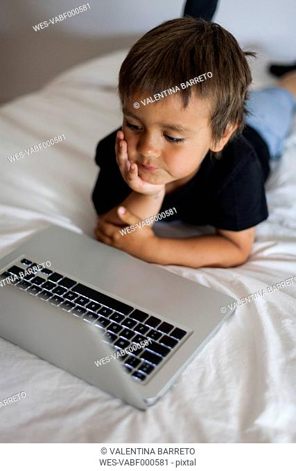 Smiling little boy lying on bed using laptop